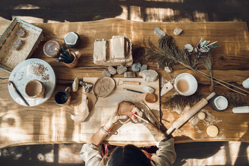 Craftsperson Concept. Young woman making pottery indoors sitting using modeling tool to create pattern on cup top view workplace