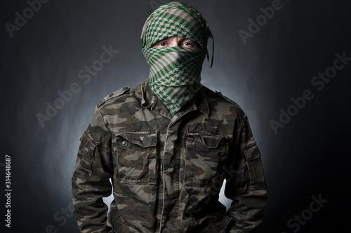 Cuadros en Lienzo Terrorist in military uniform and mask on dark background