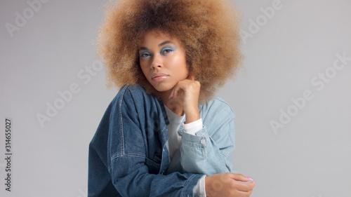 closeup portrait in studio mixed race black woman in denim oversized shirt and huge afro hair watching to the camera Blue eye fashin makeup