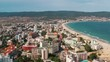 Sunny Beach, Bulgaria. Beachfront summer resort buildings beach. Tourist resort sea coast many people resting, umbrellas sand, blue water in summer blue sky and small mountains drone flying forward
