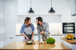 Leinwanddruck Bild - Young charming smiling caucasian woman in apron standing in kitchen and cutting cucumber while talking with her boyfriend. Man holding cherry tomato and talking about healthy lifestyle.