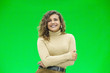 Leinwandbild Motiv Happy young woman with a cute smile standing on green background with copy space.