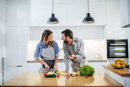Fototapeta Young charming smiling caucasian woman in apron standing in kitchen and cutting cucumber while talking with her boyfriend. Man holding cherry tomato and talking about healthy lifestyle. obraz