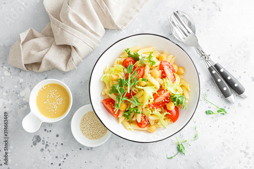 Fotografie, Obraz Pasta salad with fresh tomato, chickpea, lettuce and pea sprouts in lunch bowl