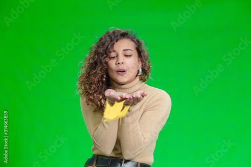 Papel de parede A young girl blows yellow autumn leaf away from her palms, standing against green background