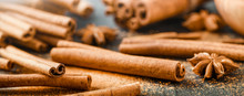 Cinnamon Panorama Or Wide Banner Concept. Cinnamons Stick And Powder On Dark Stone Table Detail.