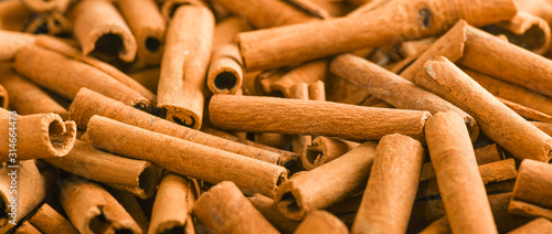 Fototapeta Cinnamon stick background wide baner or panorama top view. obraz