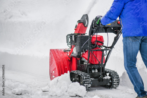 Photo Man clearing or removing snow with a snowblower on a snowy road detail