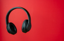 Black Headphones On A Red Background. Minimal Concept.