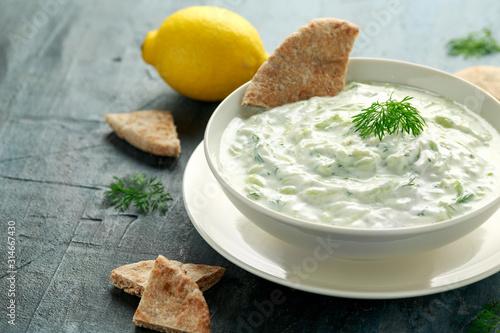 Tzatziki dip sauce with greek yogurt, garlic, dill and cucumber in white bowl Canvas Print