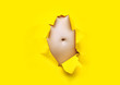 canvas print picture - Male fat, flabby stomach in a torn aperture of yellow paper. The concept of beer belly, gluttony and cellulite. Copy space.