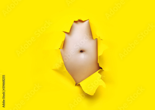 Male fat, flabby stomach in a torn aperture of yellow paper Canvas-taulu