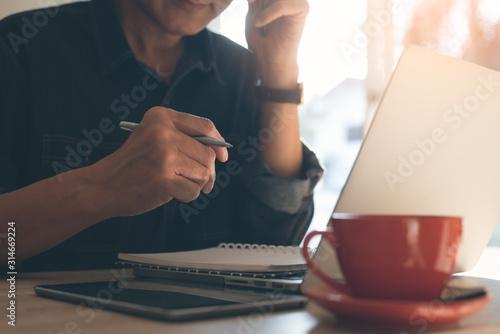 Fotografie, Tablou  Businessman writing on notepad using smartphone