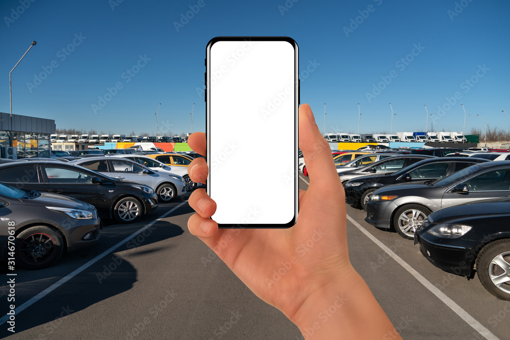 Fototapeta Hand with phone on a background of rows of cars. Car sales.