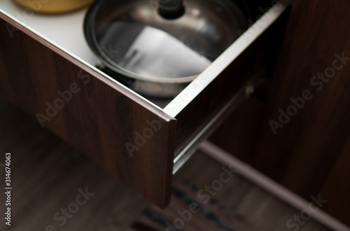 Fotomural Metal chromed pots in a drawer in a modern kitchen.