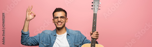 Cuadros en Lienzo Panoramic shot of man with acoustic guitar smiling at camera and showing okay is