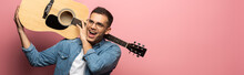 Panoramic Shot Of Excited Man With Acoustic Guitar Looking Away On Pink Background