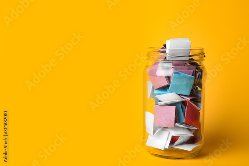 Fotografiet Glass jar full of folded paper sheets on yellow background, space for text