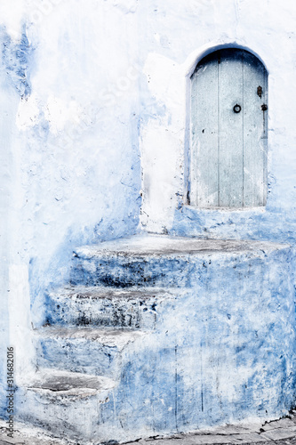 Fotografía Stone staircase with old, wooden, blue door in Chefchaouen, Morocco