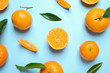 Flat lay composition with fresh ripe tangerines and leaves on light blue background. Citrus fruit