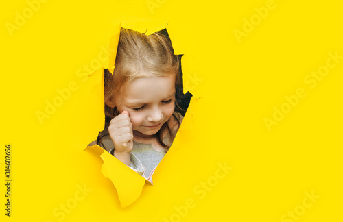 Fototapeta  The little caucasian red-haired girl screams and cry desperately from fear and fright, peering out from yellow paper in the center