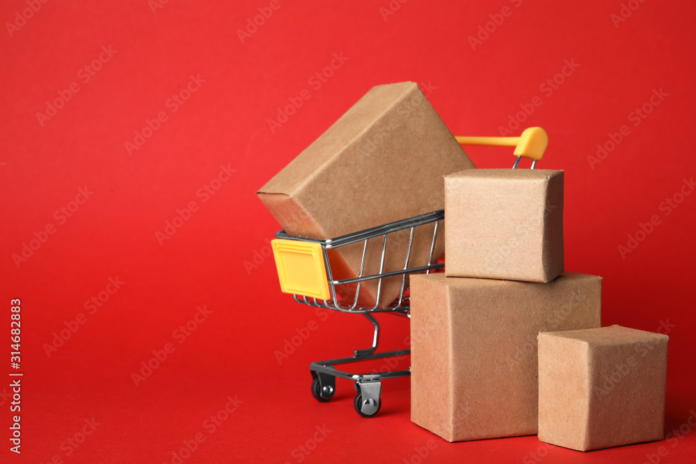 Fototapeta Shopping cart and boxes on red background, space for text. Logistics and wholesale concept