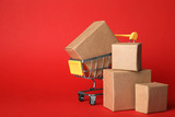 Fototapeta Kawa jest smaczna - Shopping cart and boxes on red background, space for text. Logistics and wholesale concept