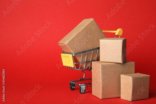 Obraz Shopping cart and boxes on red background, space for text. Logistics and wholesale concept - fototapety do salonu