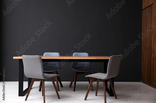Modern empty wooden table near black wall Canvas Print