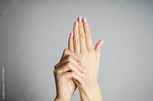 Obraz Spa and Manicure concept. Beautiful hands of a young girl with beautiful manicure on a gray background - fototapety do salonu