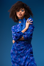 Attractive African American Woman In Dress Looking At Camera Isolated On Blue