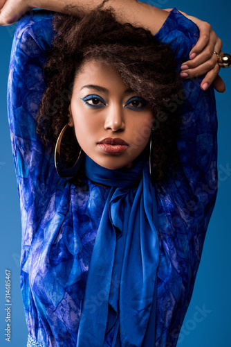 stylish african american woman with makeup in dress looking at camera isolated on blue Wall mural