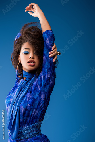 stylish african american woman in dress with closed eyes isolated on blue Wall mural