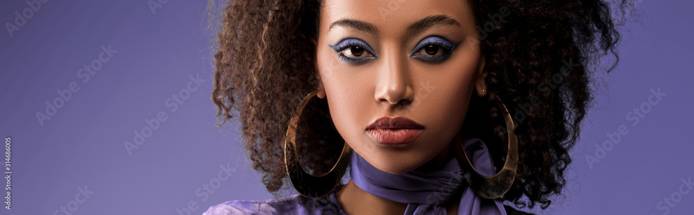 Fototapeta panoramic shot of attractive african american woman with earrings looking at camera isolated on purple