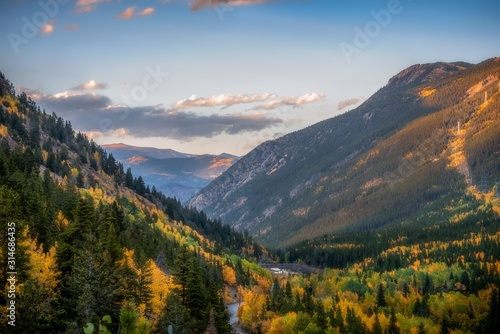 Beautiful scenery of a green landscape with colorful trees surrounded by rocky mountains