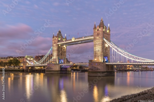 Low angle shot of the famous historic Tower Bridge in London during evening time