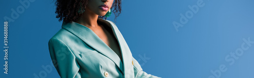 Fotografía panoramic shot of african american woman in suit isolated on blue