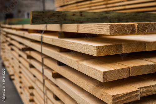 Fotografiet Piles of wooden boards in the sawmill, planking