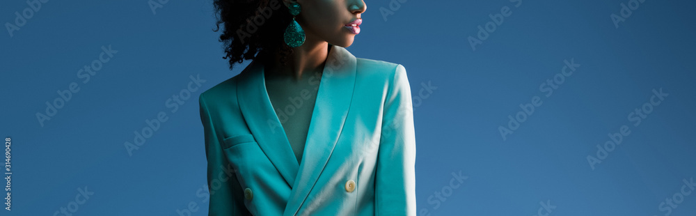Fototapeta  panoramic shot of african american woman in suit isolated on blue