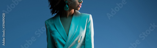panoramic shot of african american woman in suit isolated on blue