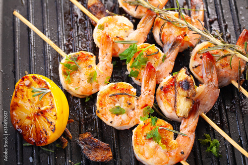 Fototapeta grilled shrimp on skewers. Grilled seafood on skewers with spices, herbs and lemon. delicious prawn. Grill. The iron grill. close up obraz