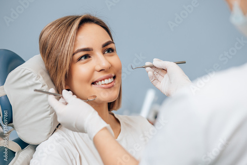 Obraz na plátně attractive woman with short hair sit in dental office and look at doctor with confidence, she has perfect smile