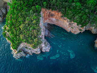 Aerial view of a steep cliff, unspoiled nature of the Montenegro coast. Sea caves and inlets alternate on the Mediterranean coast