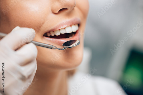 dental examination of young female on visiting doctor  going to treat. Dentist use special mirror for examination