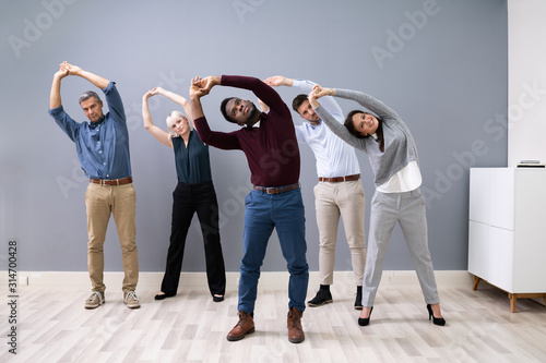 Fototapeta Businesspeople Doing Stretching Exercise At Workplace
