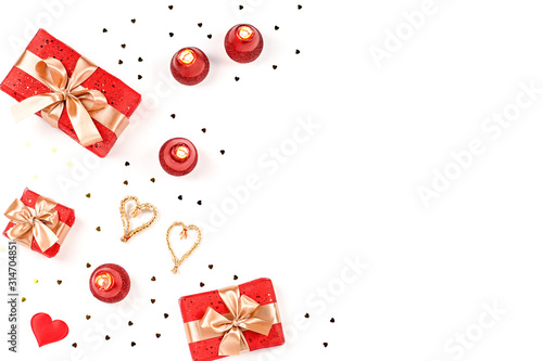 Fototapeta Creative Valentine's Day greeting card with red decorations and gift boxes, golden heart confetti on white background, copy space, top view obraz na płótnie