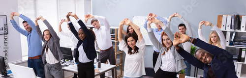 Young Businesspeople Doing Stretching Exercise At Workplace Fototapete
