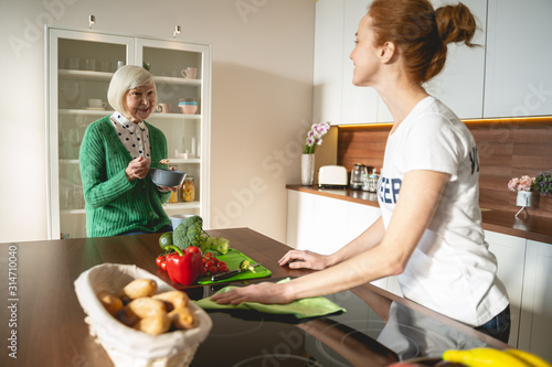 Fototapeta Delighted young volunteer cleaning kitchen for pensioner obraz