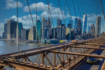 New York skyline from Brooklyn Bridge with clouds in sky in background