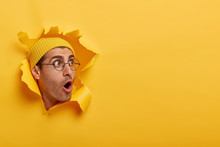 Stunned Man Looks With Great Surprisement Or Fear Aside, Opens Mouth Widely, Wears Hat And Round Glasses, Looks Through Paper Hole, Isolated Over Yellow Background. Shocking Relevation Concept